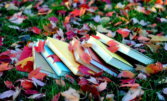 College textbooks are strewn among green grass and colorful fall leaves.