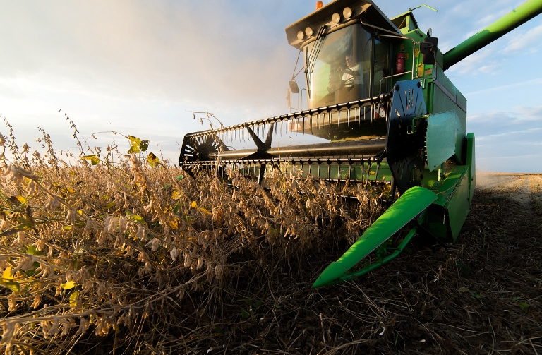 A John Deere combine cuts a swath of dry corn in the field, against a bright sun.