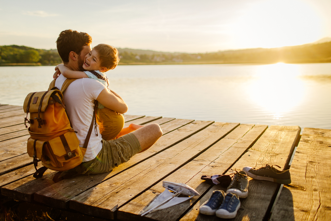 A young father and son sit on a sun-bathed lake dock, sharing a hug. The sun is setting and casts a golden light on them.