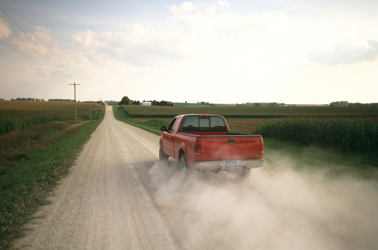 a red pickup truck drives down a dusty gravel road in mid-summer. Young green corn borders both sides of the road.
