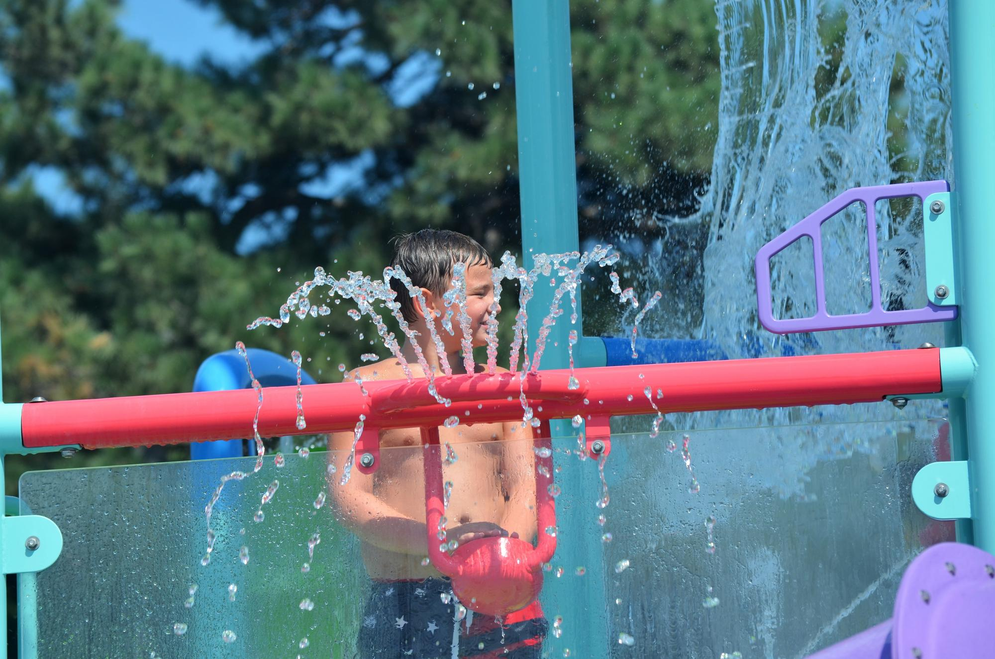 A young boy enjoys a water feature at Geneva Aquatic Center in Geneva, NE