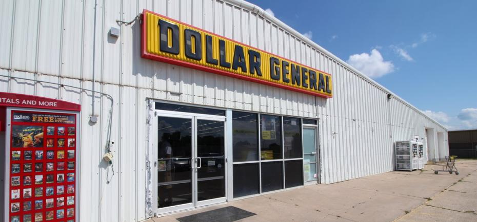 An exterior picture of a commercial building for sale in Geneva. The large building has a white tin exterior and currently houses a Dollar General store.