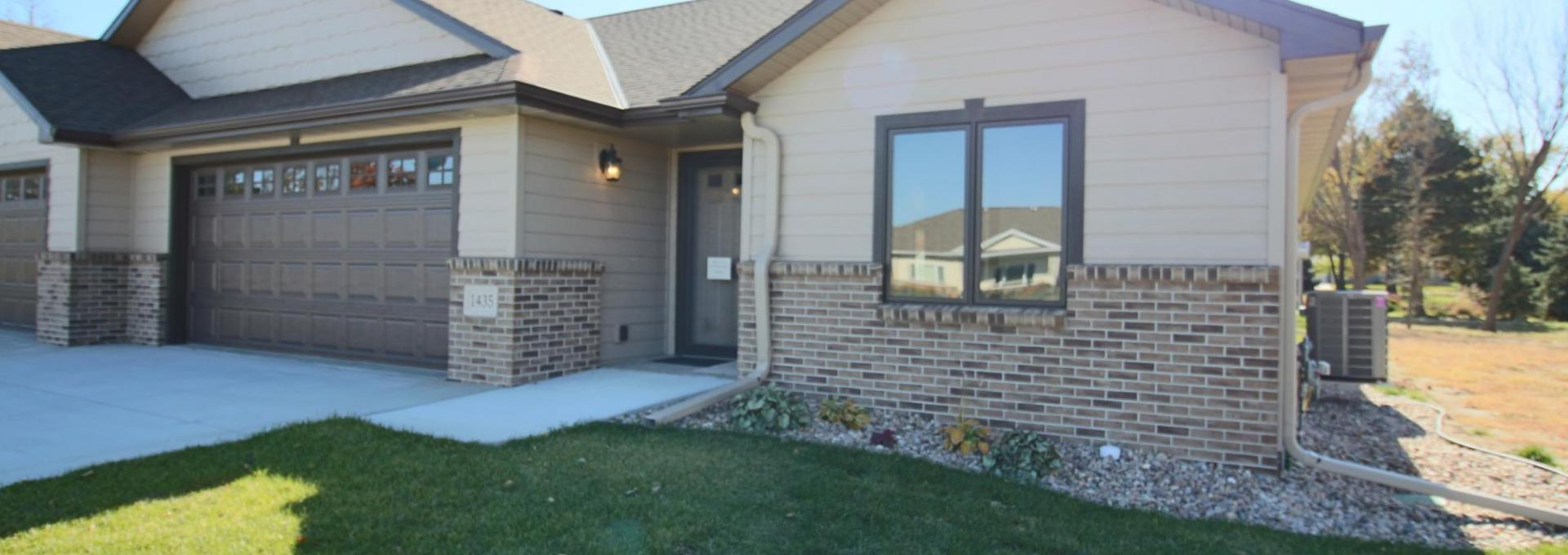 New construction townhome in Geneva, Ne., features partial brick cladding, arched roof line and spacious garage