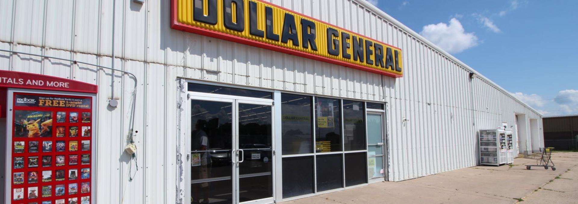 A commercial building for sale in Geneva, NE is pictured. Currently housing a Dollar General store, this 10,000+ square-foot building has a white tin exterior and a large parking lot.