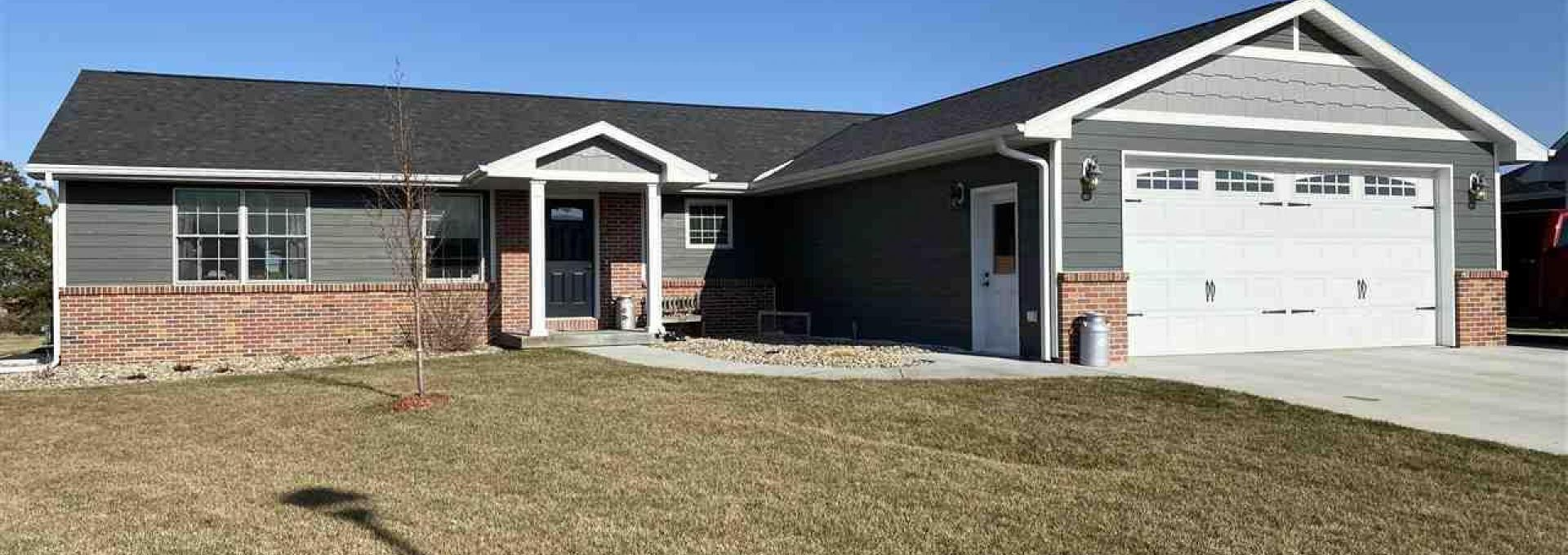 A new ranch home with a gray siding/brick exterior is pictured for sale near the Fillmore Central Elementary School.