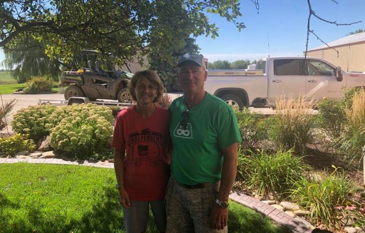 Ron and Rona Volkmer are pictured in their yard, posing in the shade of a large tree surrounded by landscaping. Both wear colorful T-shirts and khaki shorts.