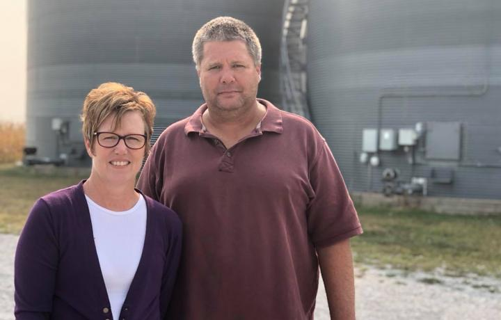 Brian and Nicole Nedrow are pictured near bins on their farm near Geneva. It is a bright September day. Nicole wears a purple cardigan and white T-shirt. Brian wears a purple polo shirt.
