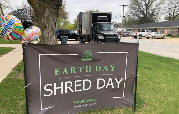 A gray and green Shred Day for Earth Day banner is shown in the foreground. The Paper Tiger mobile shredding truck sits in the background.