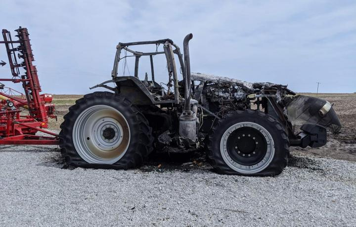 The Nedrows' blackened tractor sits against a bright blue sky following a tractor fire in April of 2020. The planter behind it is largely unscathed.