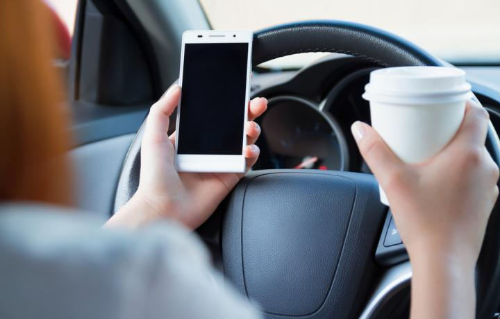This picture is a close-up shot of a steering wheel in a car. In the female driver's hands are a cell phone and a cup of coffee, held as she drives.