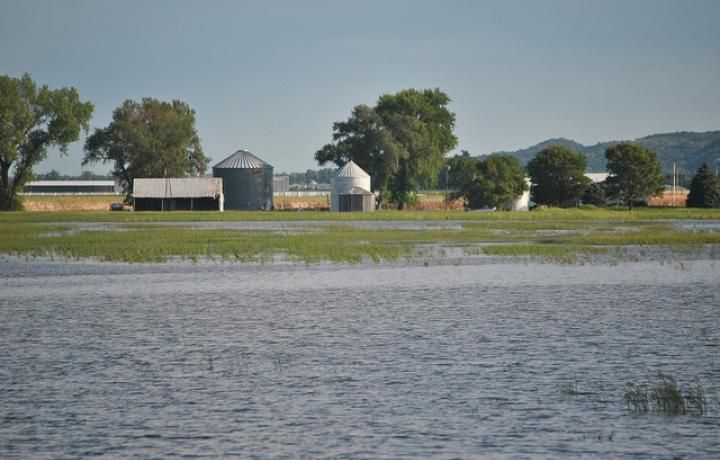 A Nebraska farm with flooded acres of cropland in the foreground and a house and barn in the background.