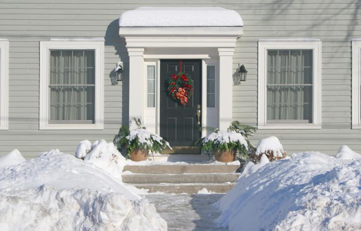 A heavy snow decorates the front yard and entryway of this pretty gray house.