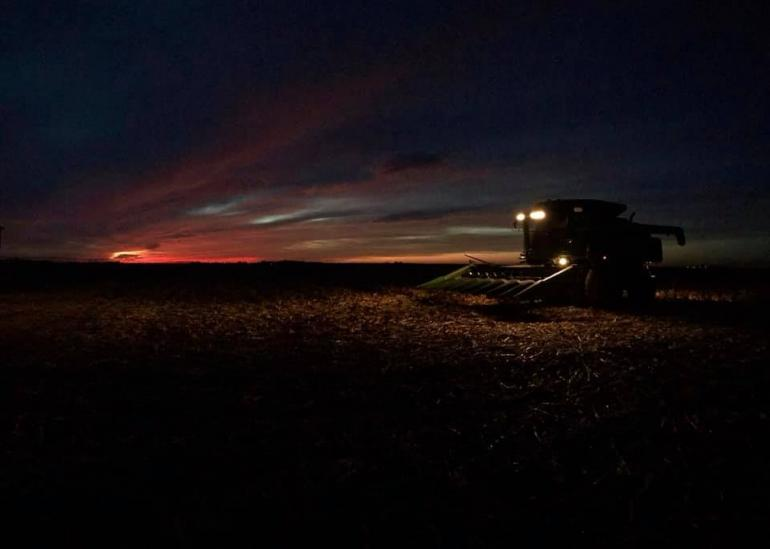 The camera captures the last rays of a fall harvest day. The sky is almost black, with the last reds and oranges sinking into the horizon.