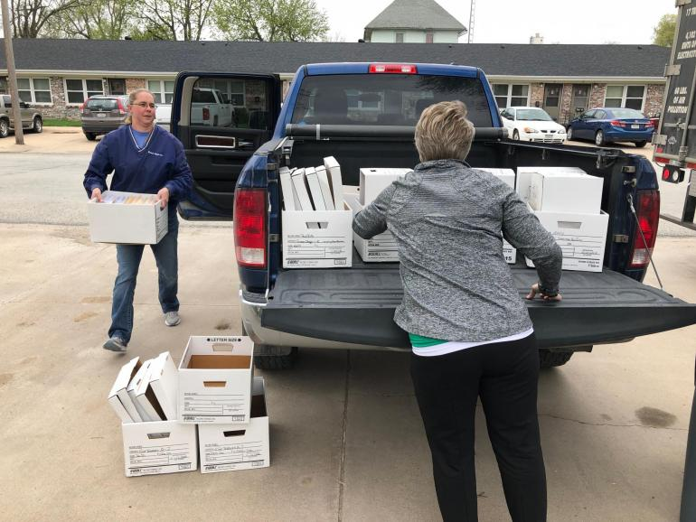 A Fortify Group customer carries a box of old files and documents to the curb, while a Fortify employee helps unload a pickup bed full of more white boxes.