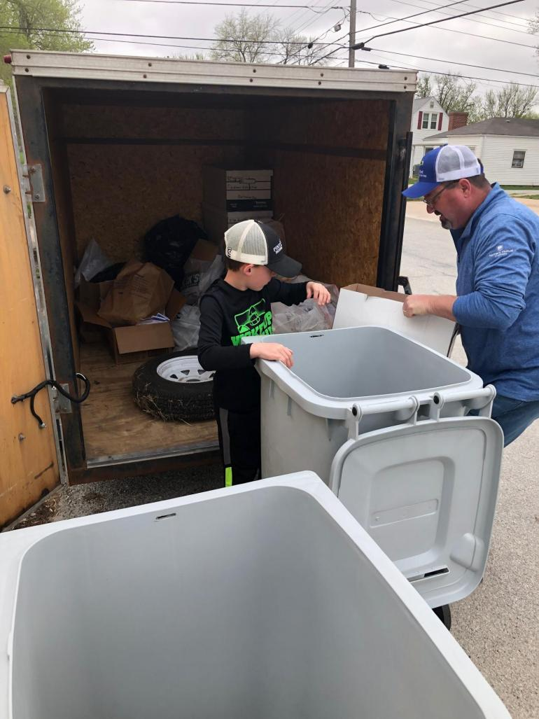 A Fortify employee and his grandson unload paper products (gathered in shickley) from an enclosed trailer.