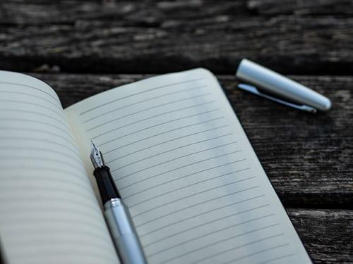 A lined notebook and pen are pictured on a wooden table.