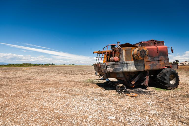 A burned, unusable red combine remains in a barren field following a combine fire. The sky above is a vivid blue.