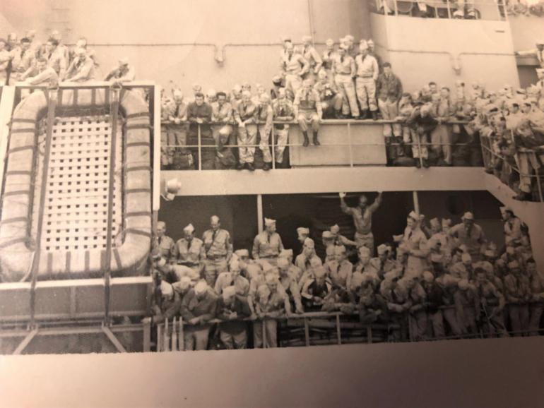 A ship is crowded with joyful soldiers returning home from the Korean war