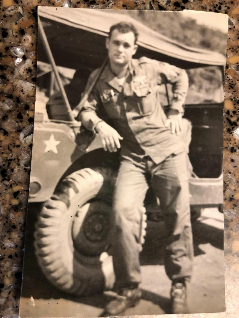 young Tanny Reinsch is picture in the Korean War. In his soldier's uniform, he leans against an army jeep for the picture.