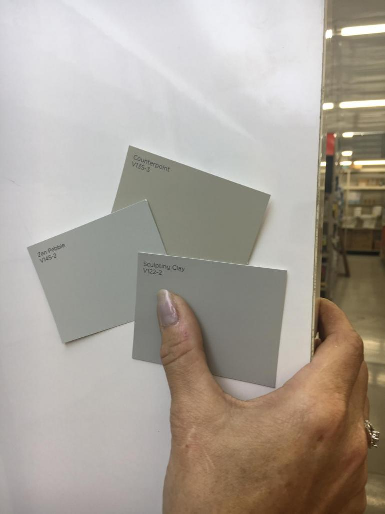 Three beige and gray paint strips are held up to a white background. They are the most popular neutral colors sold at Geneva Home Center.