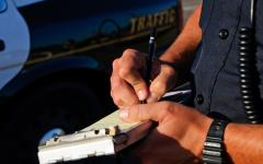 This is a close shot of a law enforcement officer's hands and he writes a citation.