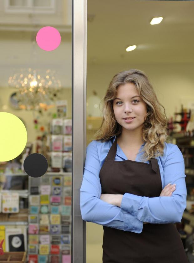 female owner standing in front of shop