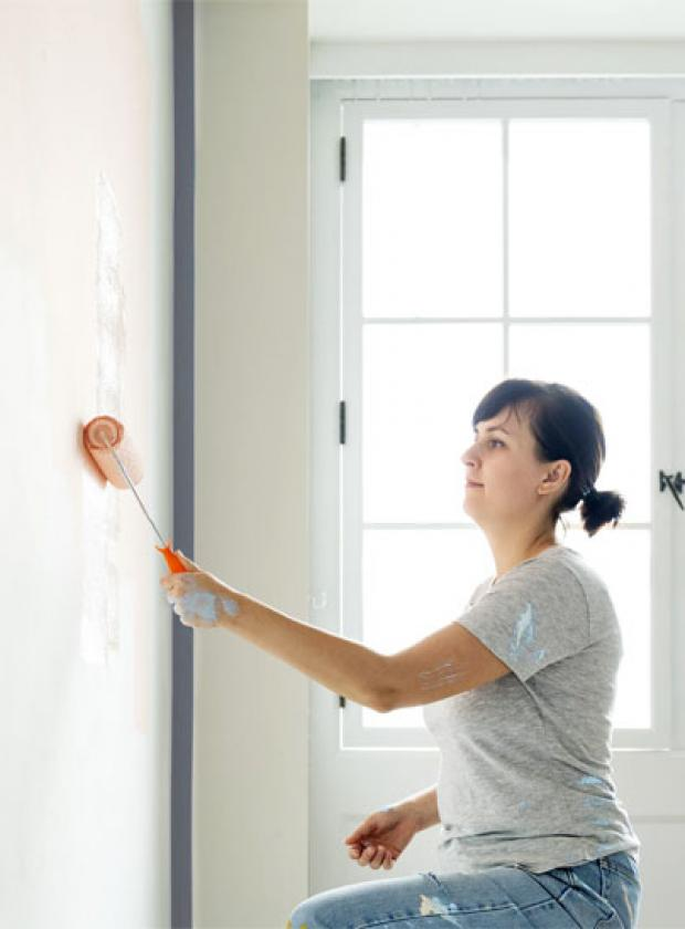 woman painting walls with paint roller