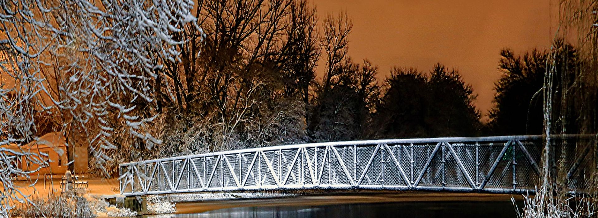 The glow of the setting winter sun contrasts nicely with snow covered trees and the bridge across 'Boys Pond' in Geneva, Neb.