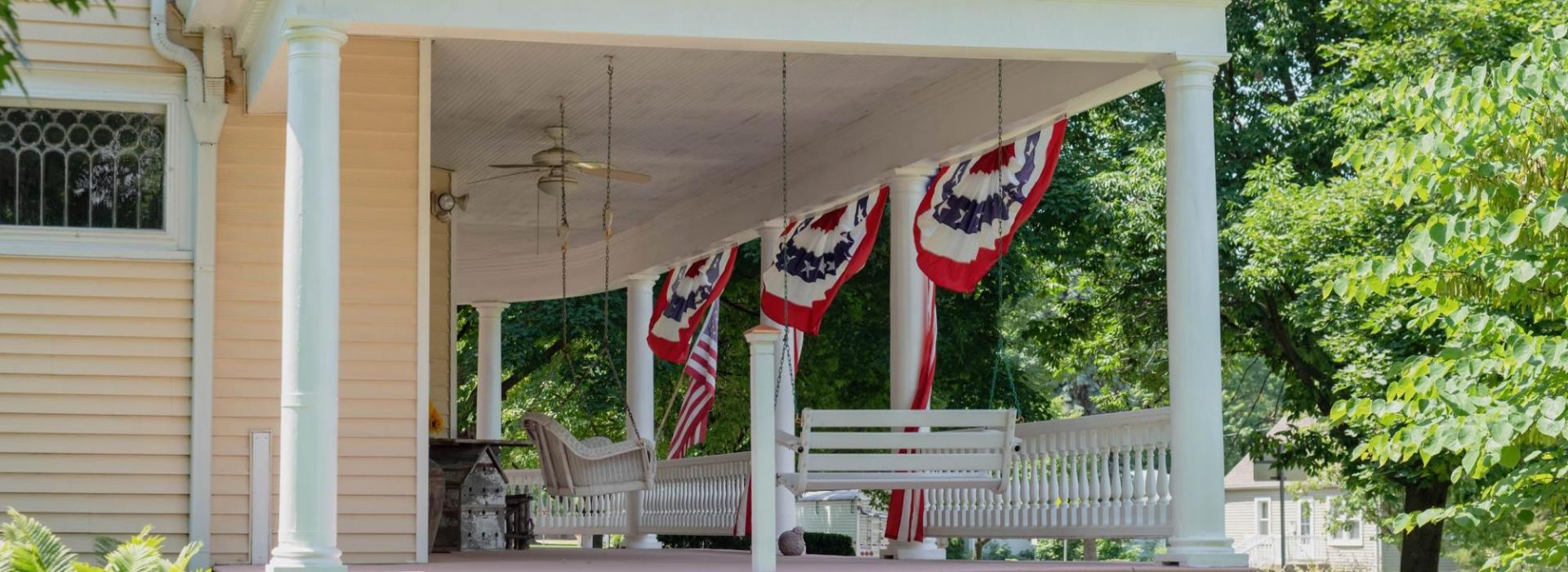 The wide front porch of a historic home is pictured, decorated with American flags.