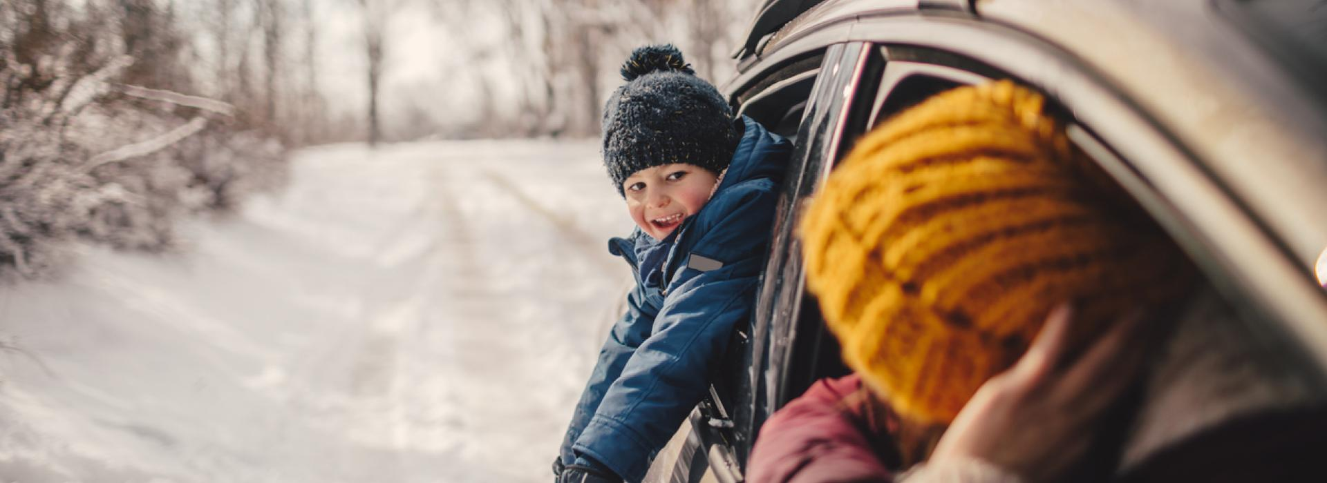 A family on a wintry road trip is pictured taking a break in their car on a country road. A young boy leans out the back window, dressed in a blue snowsuit and stocking cap.
