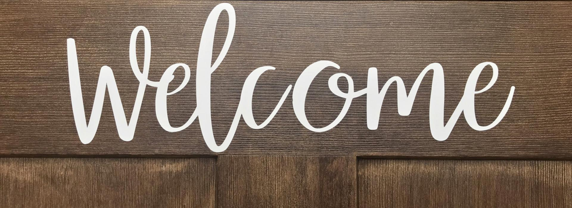 'Welcome' is written in friendly cursive letter. The white letters stand out against a Craftsman-style entry door.
