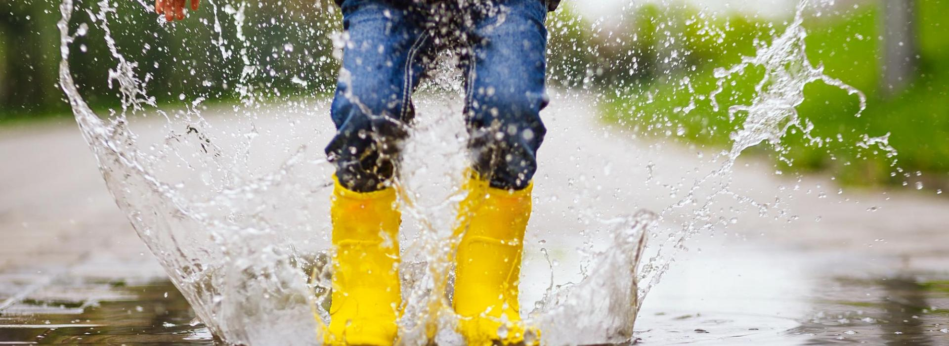 A young child splashes in puddle in a lane, wearing bright yellow boots and a navy coat.