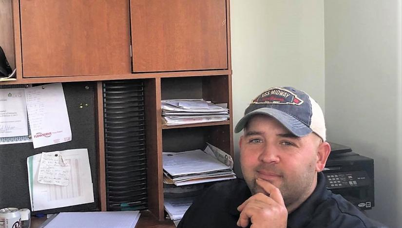 Brett Beavers, owner of Beavers Dairy, is seated in his office. A image of a Holstein cow is pictured on the cabinet behind him.